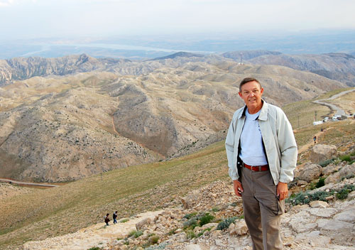 Approach the top of Mount Nemrut with the Euphrates Valley below.