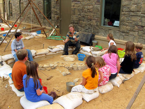 Dr. Fleming explains the archaeological artifacts to the kids.