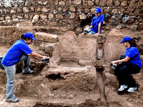 Three excavators working on the Roman bathhouse.