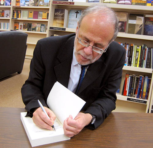 Richard Bauckham signs a book. Photo by Ferrell Jenkins.