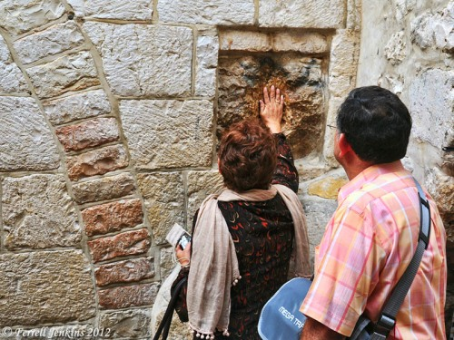 A woman places her hand on a stone at the fifth station of the cross. Photo by Ferrell Jenkins.