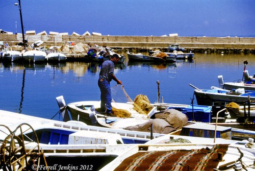 A fisherman works with his nets in the small harbor of Tyre. Photo by Ferrell Jenkins.