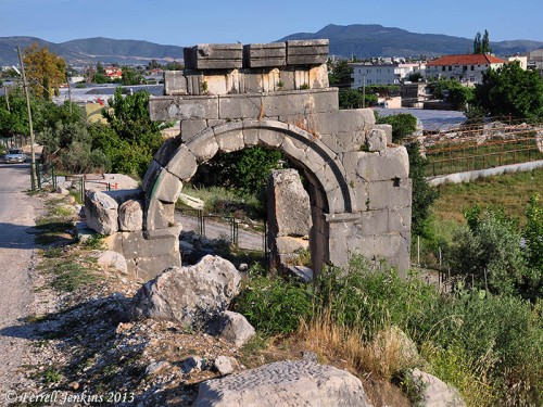 Arch built by Vespasian partially below modern road level. Photo by Ferrell Jenkins.