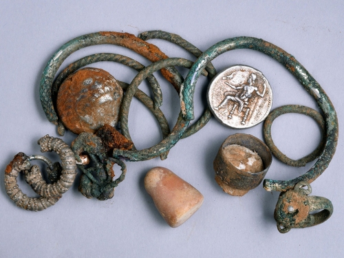 A general picture of the cache of silver objects: two coins of Alexander of Macedon, three rings, four bracelets, two decorated earrings, three other earrings (probably made of silver) and a small stone weight. Photographic credit: Clara Amit, courtesy of the Israel Antiquities Authority.