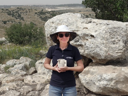 . IAA archaeologist Jenny Marcus holding a chalk cup from the time of the Second Temple period which was discovered in the estate house. Photographic credit: Avraham Tendler.