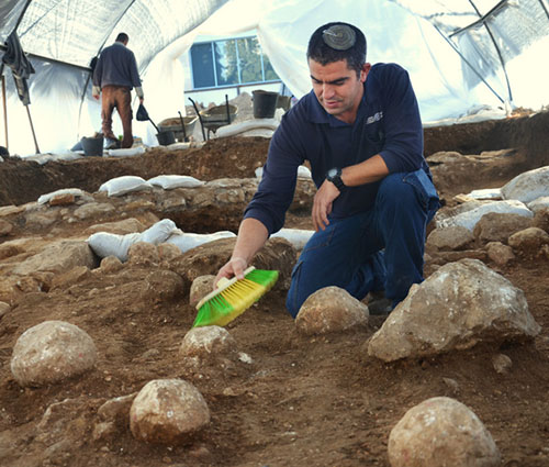 Kfir Arbib, excavation director on behalf of the Israel Antiquities Authority, cleans one of the sling stones. Photographic credit: Yoli Shwartz, courtesy of the Israel Antiquities Authority.