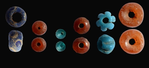 Colored beads that were uncovered in the archaeological excavation inside the dolmen. Credit: Shmuel Magal, courtesy of the Israel Antiquities Authority.