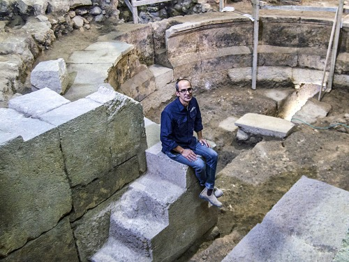 Dr Joe Uziel of the Israel Antiquities Authority, sitting on the steps of the theater structure. Photograph: Yaniv Berman, courtesy of the Israel Antiquities Authority.