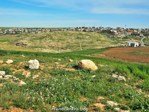 The green hill in the foreground is the ancient site of Dibon. The view is to the east. The modern town of Dhiban, Jordan, is in the distance. Photo by Ferrell Jenkins.